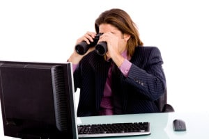 portrait of businessman looking monitor through binocular against white background